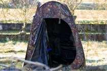 Der Eingangsbereich ist geschützt mit einer Zelttür und dahinter verbirgt sich noch zusätzlich eine Tarnvorrichtung, welche ebenfalls mit einem Reisverschluss geöffnet werden kann. Das Einmann-Tarnzelt hat ausreichend Platz.