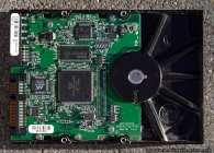 Die SATA-Festplattenelektronik mit einem etwas eingestaubten Gehäuse. Die Festplatte lief in einem Festplattenkäfig mit zusätzlichem Lüfter. Für die heutigen Festplatten, die eine ziemliche Wärme entwickeln, ist ein Lüfter empfehlenswert. Wenn man keinen Festplattenkäfig mit Aufnahme für einen Lüfter besitzt, kann man in diversen Computershops Festplattenkäfige mit Lüfter für die 5 1/4 Zoll Einbauschächte erwerben. Diese Einbaukäfige nehmen meist zwei (2) manchmal auch bis zu drei (3) 5 1/4 Zoll Schächte in Anspruch. In die zusätzlichen Festplattenkäfige passen drei (3) und mehr Festplatten, die vom Frontlüfter ausreichend gekühlt werden. Dabei wird die 'kühle' Luft von vorne (außen) angesaugt und über die gesamte Festplatte hinwegtransportiert. Einige Modelle besitzen noch zusätzliche Luftfilter, damit der Staub gefiltert wird und nicht ins Gehäuseinnere gelangt. Abgesetzter Staub auf den Bauteilen vermindert die Kühlung der PC-Komponenten, deshalb sollte man den Rechner von Zeit zu Zeit öffnen (Seitenwand) und die Bauteile entstauben. Wir benutzen teilweise einen großbürstigen Pinsel und einen Staubsauger, den wir auf minimaler Saugleistung stellen. Vorsicht mit Staubsaugern, diese können, wenn die Saugleistung zu stark ist, größeren Schaden anrichten.