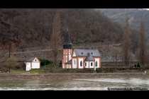 Es wird vermutet, dass die Clemenskapelle früher im Ort stand und als Pfarrkirche fungierte. Wegen der häufigen Hochwasser wurde die Ortschaft Trechtingshausen auf einen höher gelegenen Bereich verlegt. Die Klemenskapelle ist eine spätromanische Pfeilerbasilika aus dem frühen 12. Jahrhundert, die heute als Friedhofskirche dient und am Rheinufer liegt. Im inneren der Kapelle befinden sich noch Reste von Wandmalereien aus dem 14. Jahrhundert. Neben der Klemenskapelle steht das ehemalige Beinhaus der Gemeinde, die Sankt Michaelskapelle.