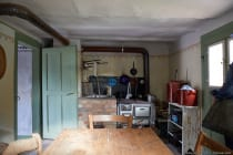 Küche in einem Wohnhaus. Die offene und sichtbare Rohrverlegung ist typisch für diese Zeit.