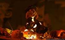 Eine Hexe mit Brille und einer dicken Knollennase auf einem Halloweenkürbis, der mit einem kleinen Teelicht beleuchtet wurde.