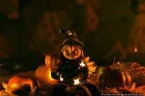 Eine Hexe inmitten von Kürbissen, die einen Kürbis in der Hand hält. Der Dekoartikel findet zur Halloweenzeit platz auf dem Wohnzimmertisch.