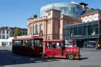 Die Touristik-Bahn startet zirka alle 70 Minuten ab 10.30 Uhr am Gutenbergplatz. Im Hintergrund ist das Staatstheater Mainz am Gutenbergplatz 7, welches zwischen den Jahren 1829 und 1833 erbaut wurde. Im Jahre 1989 bis 2001 wurde das ehemalige Stadttheater zum Staatstheater erweitert, umgebaut und erhielt eine Glaskuppel.