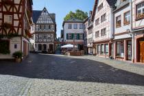 """Der Platz """"im Kirschgarten"""" existiert seit 1329 und es befinden sich dort parallel platzierte Fachwerkhäuser. Der Kirschgartenbrunnen, auch bekannt als Madonnen-, oder Marienbrunnen besteht aus rotem Zierstein und auf diesem befindet sich die Statue der Jungfrau Maria von Harxheim (Harxheimer Madonna)."""