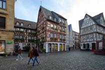 """Der Kirschgarten hieß früher """"die kleine Schöffergasse"""" und war Anfangs ein geschlossener Platz mit einem Hausbreiten Zugang zur Augustinergasse. Das im Jahre 1450 erbaute Fachwerkhaus """"Zum Aschaffenberg"""" ist das älteste, noch in Teilen erhaltene Gebäude. Im Jahre 1976 wurde das Fachwerk freigelegt und nach einer Rekonstruktion ist das Fachwerkgebäude als das älteste bekannte in Mainz wieder als solches erkennbar. Neben dem Haus Zum Aschaffenberg ist das gotische Fachwerkhaus """"Zur Wilden Gans, Zur Großen Gans, Zur goldenen Gans"""", welches ebenfalls um 1450 errichtet wurde."""