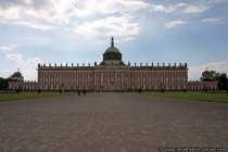 Neues Palais im Park Sanssouci. Nach Beendigung des Siebenjährigen Krieges wurde das Gebäude im Jahre 1763-1769 unter Friedrich dem Großen errichtet. Erst im deutschen Kaiserreich von 1871 bis 1918 diente das Schloss als Residenz. Friedrich der Große hatte eine gewisse Abneigung gegen diese Prunkanlage und nannte sie 'Fanfaronade', was Prahlerei bedeutet. Auf der 55 Meter hohen Kuppel tragen drei Grazien eine Königskrone, die gebettet auf einem Kissen liegt. Goldene Adler kann man auf den kleinen äußeren Kuppeln im Norden und Süden sehen. Die Königswohnung, der südliche Seitenflügel, wurde aus rotem Backstein gemauert, das restliche Mauerwerk täuscht durch einen Anstrich ein Backsteinmauerwerk vor. Von zahlreichen Bildhauern wurden über 400 Sandsteinfiguren geschaffen, welche die Schlossanlage verzieren.