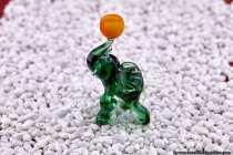 Der kleine gruene Elefant wurde im Lichtzelt mit Dekosteinen in Szene gesetzt. Als Objektiv wurde das 100mm f2,8L IS USM Macro benutzt. Bei ISO100 mit Blende8 und 1/30 Sekunde wurde der Aufbau per Funkauslöser fotografiert.