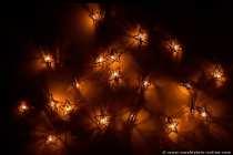 Eine Lichterkette mit Sternen mit weiblicher Kreativität an die Wohnzimmerwand gehängt