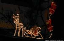 Nikoläuse am Haus hochklettern und ein Nikolaus mit Schlitten und einem Renntier auf dem Eingangsdach.