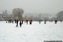 Ein zugefrorener See auf dem sich etliche Leute tümmeln.