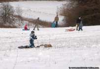 Nicht nur Kinder spielen gerne im Schnee. Der Schlitten wird ausgepackt und los geht es bergab auf dem Holzgefährt und den zwei Kufen.