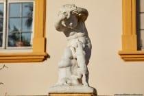 """Um das Veitshöchheimer Schloss verläuft ein säulenartiges Geländer, auch Balustrade genannt, welche geschmückt ist mit verschiedenen Vasen und Skulpturen in Kindergestalt meist mit Tieren """"Putten""""."""