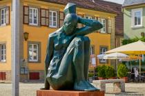 Die Großplastik mit angezogenen Beinen von dem Künstler Marco Flierl ist am Marktplatz in Weikersheim zu finden.
