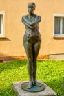 Je nach Lichtsituation, wie die untergehende Sonne oder hartes Mittagslicht und farblicher Umgebung, spiegelt sich die Farbgebung der Bronzestatue wieder.